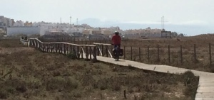 Bicyclist on wooden path in Tarifa, Spain.