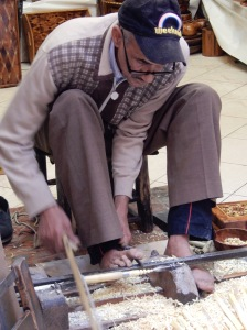 Man wood carving and using his feet to do so.